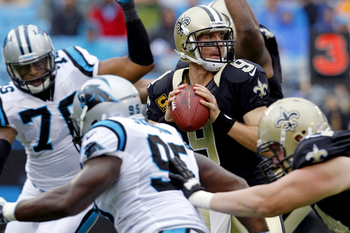 New Orleans Saints quarterback Drew Brees (9) looks to pass under pressure from Carolina Panthers' Charles Johnson (95) and Greg Hardy (76) during the first quarter of an NFL football game in Charlotte, N.C., Sunday, Sept. 16, 2012. (AP Photo/Chuck Burton)