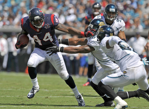 Houston Texans running back Ben Tate (44) gets around the Jacksonville Jaguars defense, including cornerback Aaron Ross, right, before running out of bounds during the first half an NFL football game on Sunday, Sept. 16, 2012, in Jacksonville, Fla. (AP Photo/Stephen Morton)