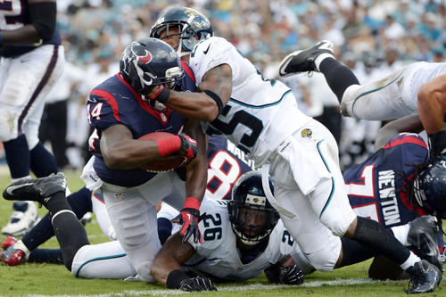 Houston Texans running back Ben Tate, left, scores a touchdown against pressure from Jacksonville Jaguars free safety Dawan Landry (26) and strong safety Dwight Lowery, right, during the first half of an NFL football game, Sunday, Sept. 16, 2012, in Jacksonville, Fla. (AP Photo/Phelan M. Ebenhack)