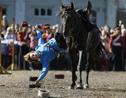A riding woman, member of a Russian traditional riding club, picks up a hat during a festival marking the 200th anniversary of the battle of Borodino which in 1812 was the largest and bloodiest single-day action of the French invasion of Russia, in St.Petersburg, Russia, Sunday, Sept. 16, 2012. (AP Photo/Dmitry Lovetsky)