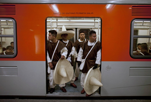 Members of the military, wearing costumes representing the 1911 revolutionary forces, stnad inside a subway train on their way to downtown Mexico City, prior to the military parade of the Independence Day celebrations, Mexico City, Sunday Sept. 16, 2012. Mexico celebrates the 202nd anniversary of its 1810 independence uprising. (AP Photo/Alexandre Meneghini)