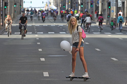 A girl rides on a wave board in one of Belgium's busiest streets, during Car Free Day, downtown Brussels, Belgium, Sunday, Sept. 16, 2012. The campaign first originated in France in 1998, aiming to promote environment-friendly transport and ease the city's traffic congestion. (AP Photo/Yves Logghe)