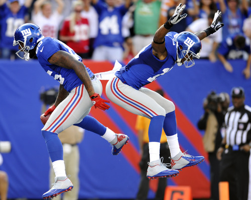 New York Giants' Martellus Bennett, left, celebrates with Ramses Barden (13) after Bennett scored a touchdown during the second half of an NFL football game against the Tampa Bay Buccaneers, Sunday, Sept. 16, 2012, in East Rutherford, N.J. The Giants won 41-34. (AP Photo/Bill Kostroun)