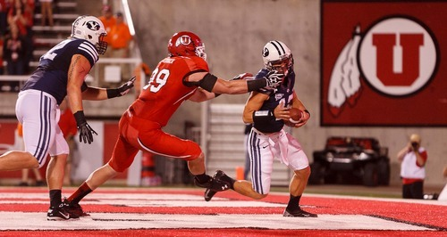 Trent Nelson  |  The Salt Lake Tribune Utah defensive end Joe Kruger (99) brings down Brigham Young quarterback Riley Nelson (13) for what would have been a safety but a face mask penalty was called during the game in Salt Lake City on Saturday, Sept. 15, 2012.