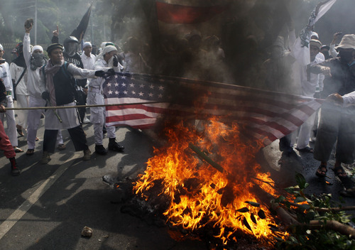 Muslim protesters burn a U.S. flag during a protest against American-made film