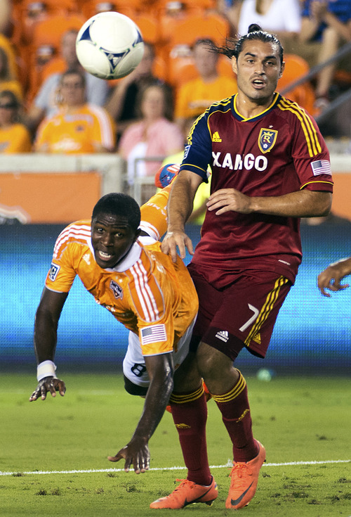 Houston Dynamo defender Kofi Sarkodie (8) dives for a ball against Real Salt Lake forward Fabian Espindola (7) during an MLS soccer match, Thursday, Sept. 6, 2012, in Houston. (AP Photo/Houston Chronicle, Smiley N. Pool)