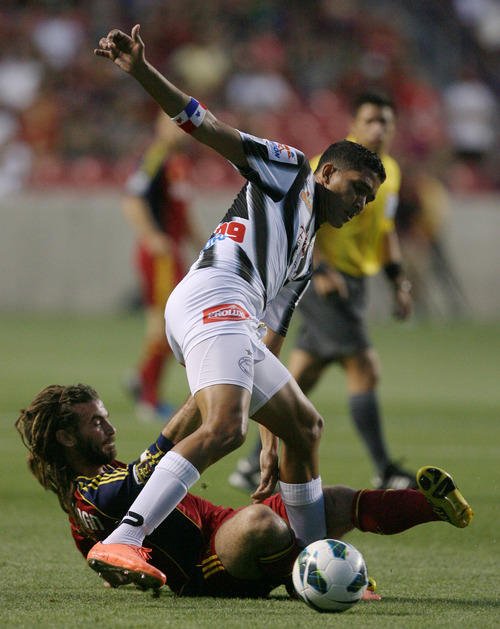 Steve Griffin | The Salt Lake Tribune   Real Salt Lake's Kyle Beckerman slides as he kicks the ball away from Tauro FC's Edwon Aguilar during a Champions League game at Rio Tinto Stadium in Sandy on Tuesday, Aug. 21, 2012.