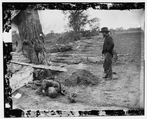 A soldier looking upon a Union soldier's grave with the body of a Confederate soldier seemingly tossed aside in Antietam, Maryland. (September 1862) Credit: Courtesy of Library of Congress