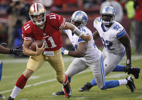 San Francisco 49ers quarterback Alex Smith, left, runs with the ball past Detroit Lions strong safety Erik Coleman, center, and defensive end Cliff Avril, right, during the third quarter of an NFL football game in San Francisco, Sunday, Sept. 16, 2012. (AP Photo/Tony Avelar)