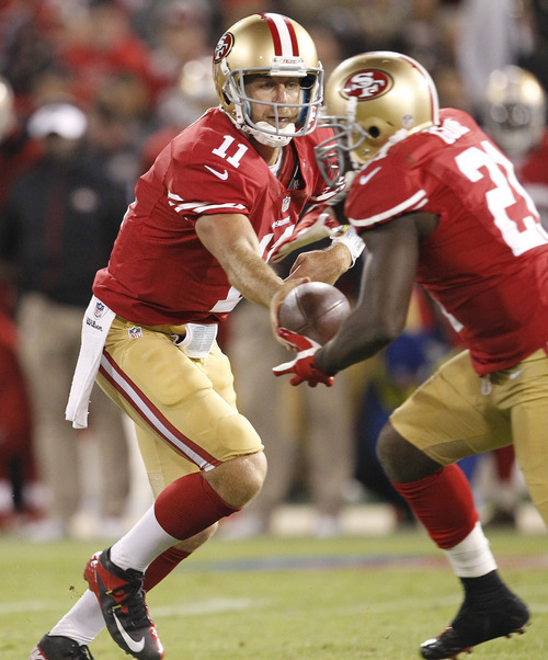 San Francisco 49ers quarterback Alex Smith, left, hands off the ball to running back  Frank Gore, right, during the fourth quarter of an NFL football game against the Detroit Lions in San Francisco, Sunday, Sept. 16, 2012. (AP Photo/Tony Avelar)