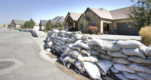 Paul Fraughton | The Salt Lake Tribune Homes that were affected by recent flooding in Saratoga Springs  have walls of sandbags along their street  for  protection.   Friday, September 14, 2012