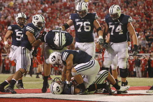 Chris Detrick  |  The Salt Lake Tribune Brigham Young Cougars tight end Kaneakua Friel (82) is surrounded by his teammates after scoring a touchdown during the second half of the game at Rice-Eccles Stadium Saturday September 15, 2012.  Utah won the game 24-21.