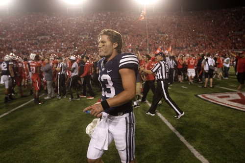BYU quarterback Riley Nelson (13) walks away from the Utah fans who prematurely rushed the field with 1 second left on the clock in the fourth quarter of an NCAA football game with Utah Saturday, Sept. 15, 2012, in Salt Lake City. Utah defeated BYU 24-21.  (AP Photo/Rick Bowmer)