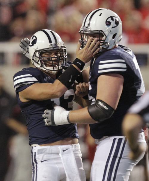 BYU quarterback Riley Nelson, left, is congratulated by offensive linesman Braden Hansen after throwing a touchdown pass during the second quarter of an NCAA college football game against Utah on Saturday, Sept. 15, 2012, in Salt Lake City. (AP Photo/Rick Bowmer)