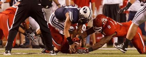 Trent Nelson  |  The Salt Lake Tribune Brigham Young quarterback Riley Nelson (13) recovers his fumble as he's sacked by Utah defensive end Joe Kruger (99) during the game in Salt Lake City on Saturday, Sept. 15, 2012. Utah defensive end Nate Fakahafua (8 )is at right.