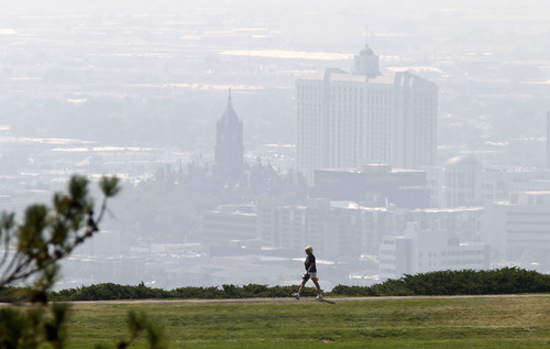 Al Hartmann  |  The Salt Lake Tribune Walker at 11th Avenue Park stands out above Salt Lake's smokey downtown Tuesday afternoon.  Low visibility and haze is smoke from wildfires in Idaho.  It was a red air day along the Wasatch front.