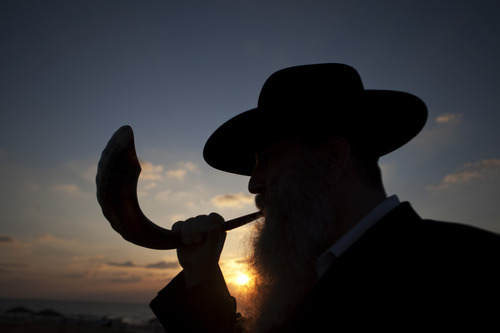 A Jew blows a shofar, Ram's horn, while others pray as they perform Tasklikh, a Rosh Hashanah ritual for casting sins upon the waters, in front of the Mediterranean sea, in Ashdod, Israel, Thursday, Sept. 29, 2011.  Tasklikh is when Jews symbolically throw their sins into moving water during the New Year holiday of Rosh Hashana. (AP Photo/Ariel Schalit)