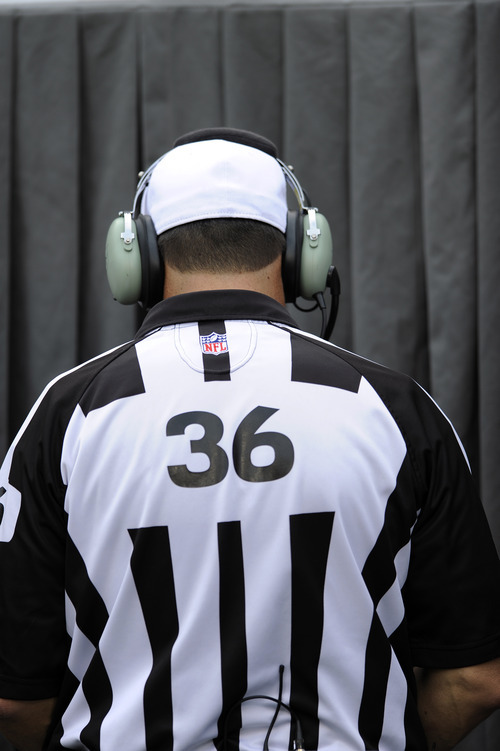 Referee Robert Frazer checks a replay in the second half of an NFL football game between the Philadelphia Eagles and the Baltimore Ravens, Sunday, Sept. 16, 2012, in Philadelphia. (AP Photo/Michael Perez)