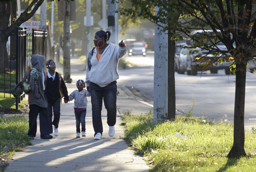 Leslie Sabbs-Kizer, right, walks her children  Nkai Melton, 8, Akaira Melton, 7, and Khaymya Smith, 3 to Bond Elementary school in Chicago, for the first day of classes Wednesday morning, Sept. 19, 2012, after Chicago teachers voted to suspend their first strike in 25 years. Union delegates voted overwhelmingly Tuesday night to suspend the walkout after discussing a proposed contract settlement with the nation's third largest school district.  (AP Photo/M. Spencer Green)