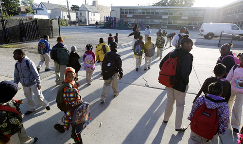 Students walk through the gates outside Benjamin E. Mays Academy,  Wednesday morning, Sept. 19, 2012, after Chicago teachers voted to suspend their first strike in 25 years. Union delegates voted overwhelmingly Tuesday night to suspend the walkout after discussing a proposed contract settlement with the nation's third largest school district.  (AP Photo/M. Spencer Green)