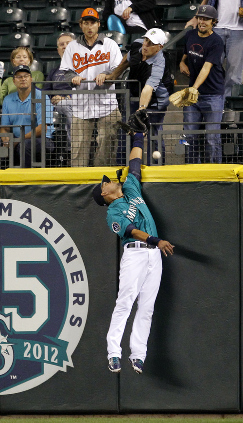 Seattle Mariners center fielder Franklin Gutierrez leaps for but isn't able to snag a two-run home run ball from Baltimore Orioles' Matt Wieters in the fourth inning of a baseball game, Monday, Sept. 17, 2012, in Seattle. (AP Photo/Elaine Thompson)