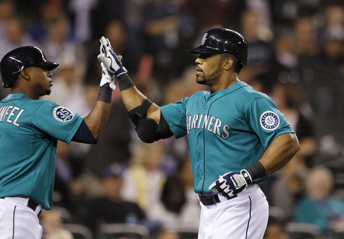 Seattle Mariners' Eric Thames, right is congratulated by Carlos Triunfel after hitting a home run against the Baltimore Orioles in the eighth inning of a baseball game Monday, Sept. 17, 2012, in Seattle. (AP Photo/Elaine Thompson)