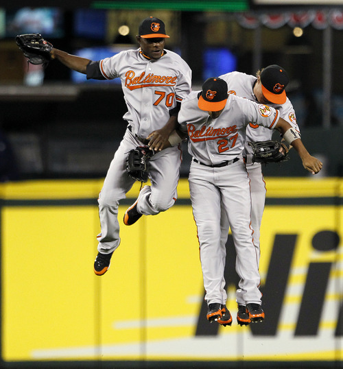 Seattle Mariners Baltimore Orioles outfielders Xavier Avery (70), Endy Chavez (27) and Nate McLouth leap together after the team beat the Seattle Mariners in a baseball game Monday, Sept. 17, 2012, in Seattle. Baltimore won 10-4. (AP Photo/Elaine Thompson)