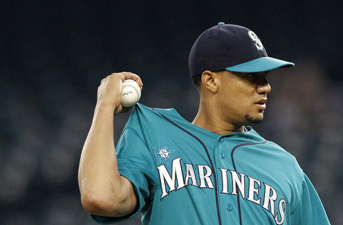 Seattle Mariners starting pitcher Hector Noesi tugs on his jersey after giving up a run to the Baltimore Orioles in the first inning of a baseball game, Monday, Sept. 17, 2012, in Seattle. (AP Photo/Elaine Thompson)