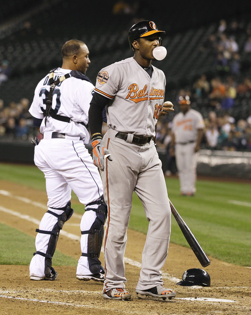 Baltimore Orioles' Adam Jones blows a bubble after striking out as Seattle Mariners catcher Miguel Olivo stands by during the seventh inning a baseball game, Tuesday, Sept. 18, 2012, in Seattle. (AP Photo/Ted S. Warren)