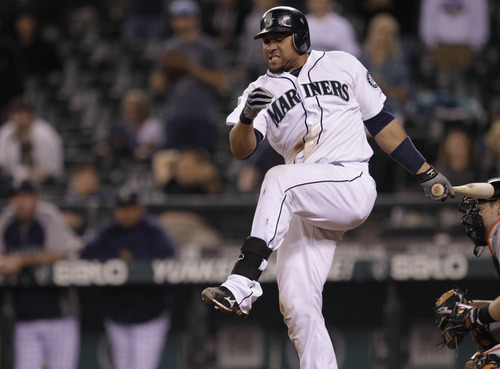 Seattle Mariners' Miguel Olivo reacts to a foul ball in the 18th inning of a baseball game against the Baltimore Orioles, in the early hours of Wednesday , Sept. 19, 2012, in Seattle. The Orioles beat the Mariners, 4-2 in 18 innings. (AP Photo/Ted S. Warren)