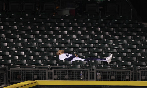 A fan rests between innings of an 18-inning baseball game between the Baltimore Orioles and the Seattle Mariners in the early hours of Wednesday, Sept. 19, 2012, in Seattle. The Orioles beat the Mariners 4-2 in 18 innings. (AP Photo/Ted S. Warren)