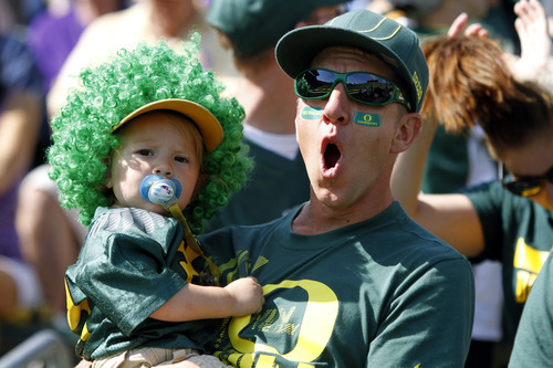 An Oregon fan reacts while holding a child during the first half of their NCAA college football game against Tennessee Tech in Eugene, Ore., Saturday, Sept. 15, 2012.(AP Photo/Don Ryan)