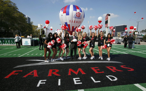 FILE - In this Feb. 1, 2011, file photo, Paul Patsis, president of Market Management for Farmers Insurance, center, poses with Los Angeles Kings cheerleaders during a ceremony naming a new proposed NFL football stadium in Los Angeles, that would be called Farmers Field under a 30-year naming-rights deal between developer AEG and Farmers Insurance Exchange. Denver-based Anschutz Co. said Tuesday, Sept. 18, 2012, that it was