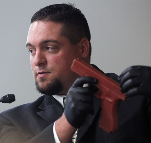 Al Hartmann  |  The Salt Lake Tribune Justin Beahauser, a forensic firearms scientist with the Utah state crime lab describes the tests he did on Eric Charlton's gun during preliminary hearing in Judge James Brady's Fourth District Court in Nephi Wednesday September 19.  The gun he is holding is a dummy model.