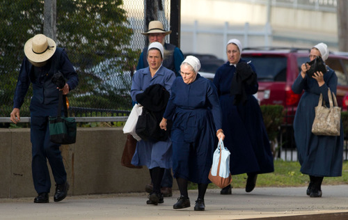 A group of Amish walk to the U.S. Federal Courthouse in Cleveland on Thursday, Sept. 20, 2012.  The jury will begin their fifth day of deliberations in the trial of 16 Amish people accused of hate crimes in hair- and beard-cutting attacks against fellow Amish in Ohio. (AP Photo/Scott R. Galvin)