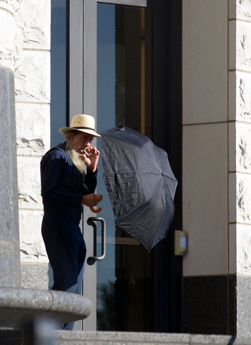 An Amish man takes a smoke break outside the U.S. Federal Courthouse in Cleveland on Wednesday, Sept. 19, 2012.  The jury finished their fourth day of deliberations without a verdict in the trial of 16 people accused of hate crimes in hair- and beard-cutting attacks against fellow Amish in Ohio. (AP Photo / Scott R. Galvin)