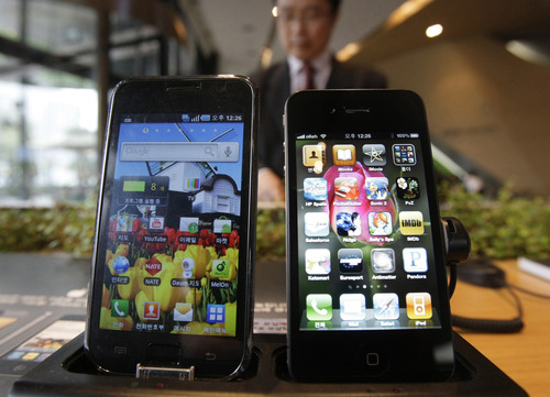 FILE-In this Friday, April 22, 2011, file photo, Samsung Electronics' Galaxy S, left, and Apple's iPhone 4 are displayed at the headquarters of South Korean mobile carrier KT in Seoul, South Korea, Friday. People who buy their first smartphones likely will narrow their choices to either an Android phone like the Galaxy S or the iPhone. (AP Photo/Ahn Young-joon, File)