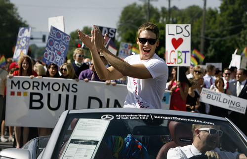 Scott Sommerdorf  |  The Salt Lake Tribune              Grand Marshal Dustin Lance Black applaudes as he leads the annual Gay Pride Parade through downtown Salt Lake City, followed by the Mormons Building Bridges group right behind, Sunday, June 3, 2012.