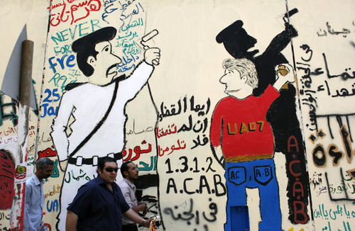 Egyptian men walk past a newly painted mural on a newly whitewashed wall in Tahrir Square, Cairo, Egypt, Thursday, Sept. 20, 2012. Under cover of darkness, a few municipality workers quietly began to paint over an icon of Egypt's revolution: a giant, elaborate public mural on the street that saw some of the most violent clashes between protesters and police over the past two years. Arabic reads