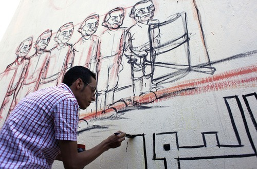 An Egyptian artist works on a mural with faces depicting ousted Egyptian president Hosni Mubarak on a newly whitewashed wall in Tahrir Square, Cairo, Egypt, Thursday, Sept. 20, 2012. Under cover of darkness, a few municipality workers quietly began to paint over an icon of Egypt's revolution: a giant, elaborate public mural on the street that saw some of the most violent clashes between protesters and police over the past two years. (AP Photo/Nasser Nasser)