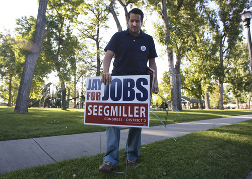 Kim Raff | The Salt Lake Tribune Jay Seegmiller's congressional campaign manager Alan Seim sets up signs for Seegmiller during a kickoff event to reach Latino voters.