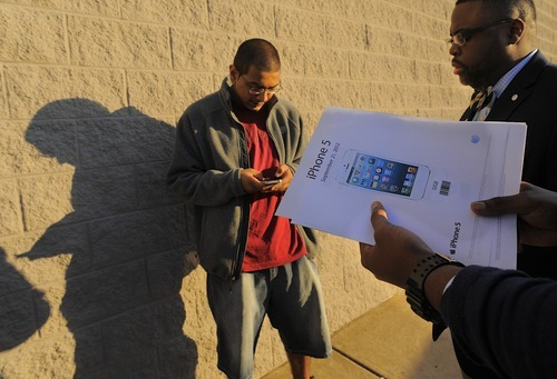 AT&T Mobility store  manager David Neal, right,  talks to customers outside the store prior to opening  to sell the new iPhone 5, Friday, Sept. 21, 2012, in Fredericksburg, Va. (AP Photo/The Free Lance-Star, Robert A. Martin)