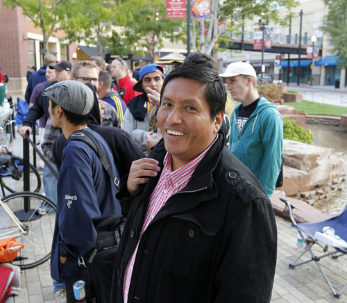 Al Hartmann  |  The Salt Lake Tribune Dino Oshley smiles in anticipation at 7:55 a.m. Friday, Sept. 21.  He was the first in line to buy the iPhone 5 that went on sale at 8 a.m. at the Apple Store at The Gateway in Salt Lake City.   He arrived at 7 p.m. last night to take the first spot that a relative held for him for 12 hours earlier.
