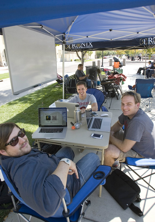 Paul Fraughton | The Salt Lake Tribune Joe Wilson (front), Jonathan Lund and Spencer Smith (right), spend their time waiting in line for the new iPhone 5 by developing applications that can be used on the new phone.   Thursday, September 20, 2012