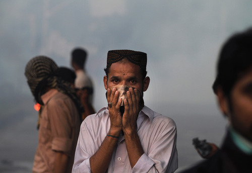 A Pakistani protester reacts to tear gas during clashes that erupted as the demonstrators tried to approach the U.S. embassy in Islamabad, Pakistan, Friday, Sept. 21, 2012. Over a dozen people were killed as tens of thousands protested against an amateurish anti-Muslim film produced in the United States and vulgar caricatures of the Prophet Muhammad published in a French satirical weekly around the country after the government encouraged peaceful protests and declared a national holiday —