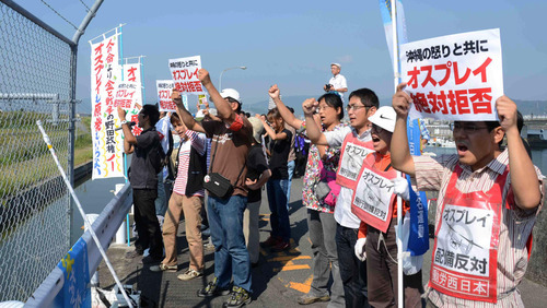 Demonstrators display signs against deployment of Osprey aircraft in Iwakuni, Yamaguchi prefecture, southern Japan Friday, Sept. 21, 2012. The U.S. Marines are conducting their first test flights of the MV-22 Osprey aircraft in Japan after months of protests there over safety concerns. (AP Photo/Kyodo News) JAPAN OUT, MANDATORY CREDIT, NO LICENSING IN CHINA, HONG KONG, JAPAN, SOUTH KOREA AND FRANCE
