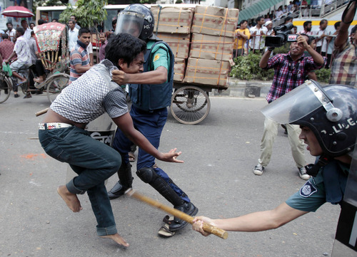 Bangaldeshi policemen detain an activist of an Islamic group during a protest in Dhaka, Bangladesh, Saturday, Sept. 22, 2012. Officials and witnesses said scores of people were injured in a clash in Bangladesh's capital between police and hundreds of Muslims who were protesting a film produced in the United States that denigrates the Prophet Muhammad. (AP Photo/A.M. Ahad)
