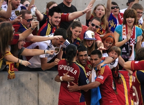 Real Salt Lake's midfielder Javier Morales, center, receives a hug from teammates Fabian Espindola, left and Paulo Junior, right after scoring against the Portland Timbers in the first half of an MLS soccer game Saturday, Sept. 22, 2012, in Sandy, Utah.  (AP Photo/Rick Bowmer)