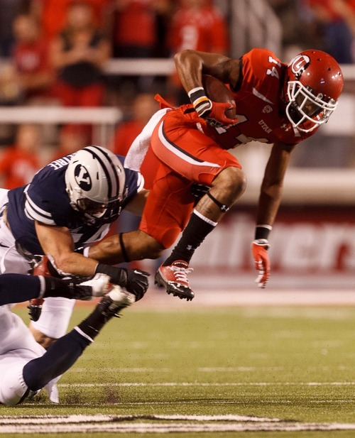 Trent Nelson  |  The Salt Lake Tribune Utah wide receiver Reggie Dunn (14) leaps away from BYU defenders during the game in Salt Lake City on Saturday, Sept. 15, 2012.