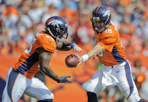 Denver Broncos quarterback Peyton Manning (18) hands the ball off to running back Willis McGahee (23) in the first quarter of an NFL football game against the Houston Texans Sunday, Sept. 23, 2012, in Denver. (AP Photo/Jack Dempsey)